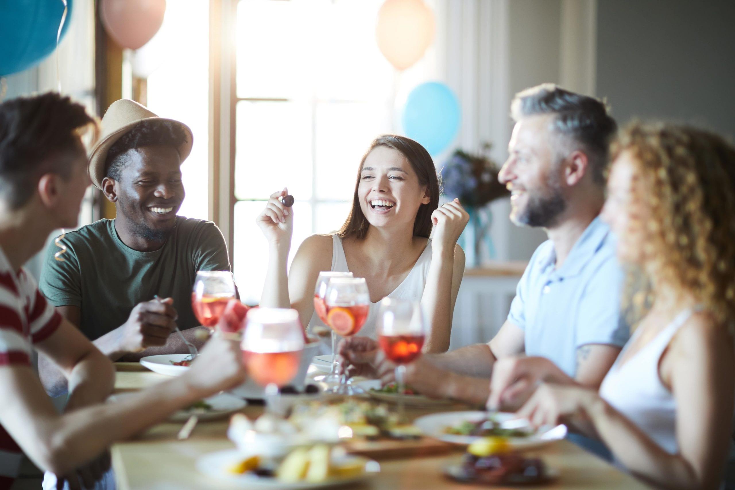 Group of friends celebrating National CBD Day over dinner