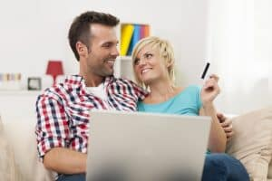 Smiling couple on laptop ready to purchase Smilyn CBD